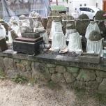 αγαλματίδια στις άκρες του δρόμου σκεπασμένα με ύφασμα που τα άγγιζαν και έκαναν ευχές